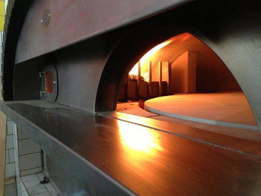 The pizza oven at La Favorita is getting hungry.