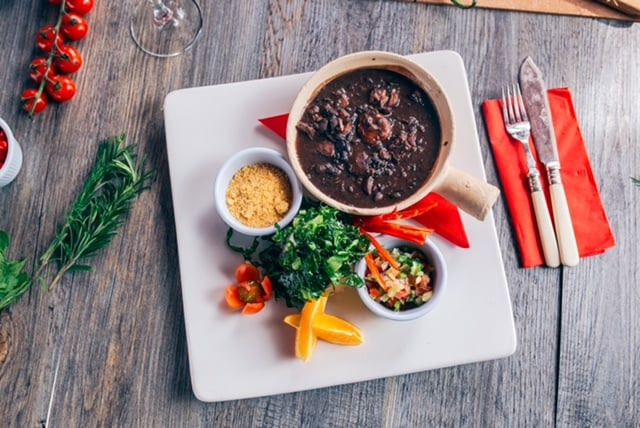 Feijoada: the traditional Brazilian feast stew with black beans, pork ribs, smoked bacon, salt beef and smoked sausage. It is served served with rice, chilli salad, flavoured cassava flour and slices of orange.