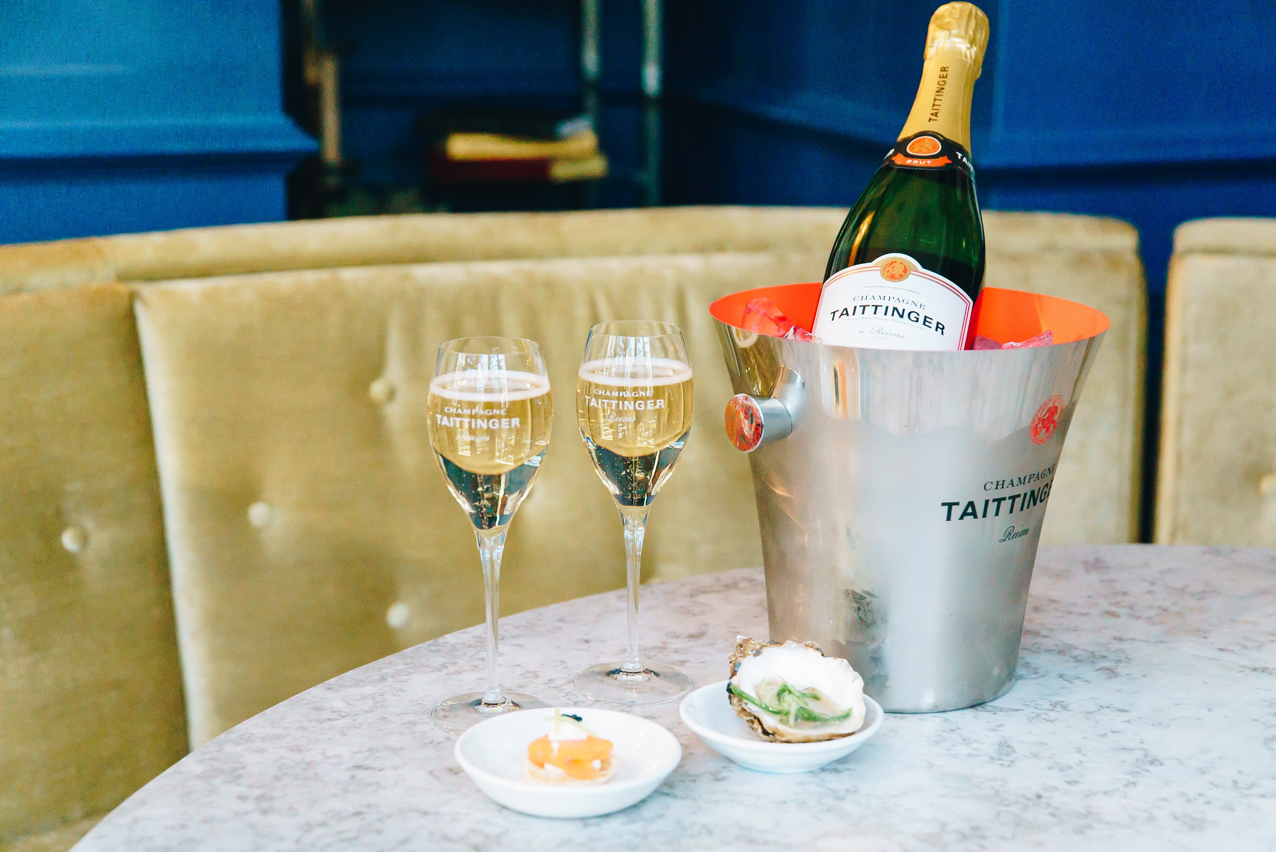 Bottle of Taittinger Nocturne Sec NC in ice bucket with canapes