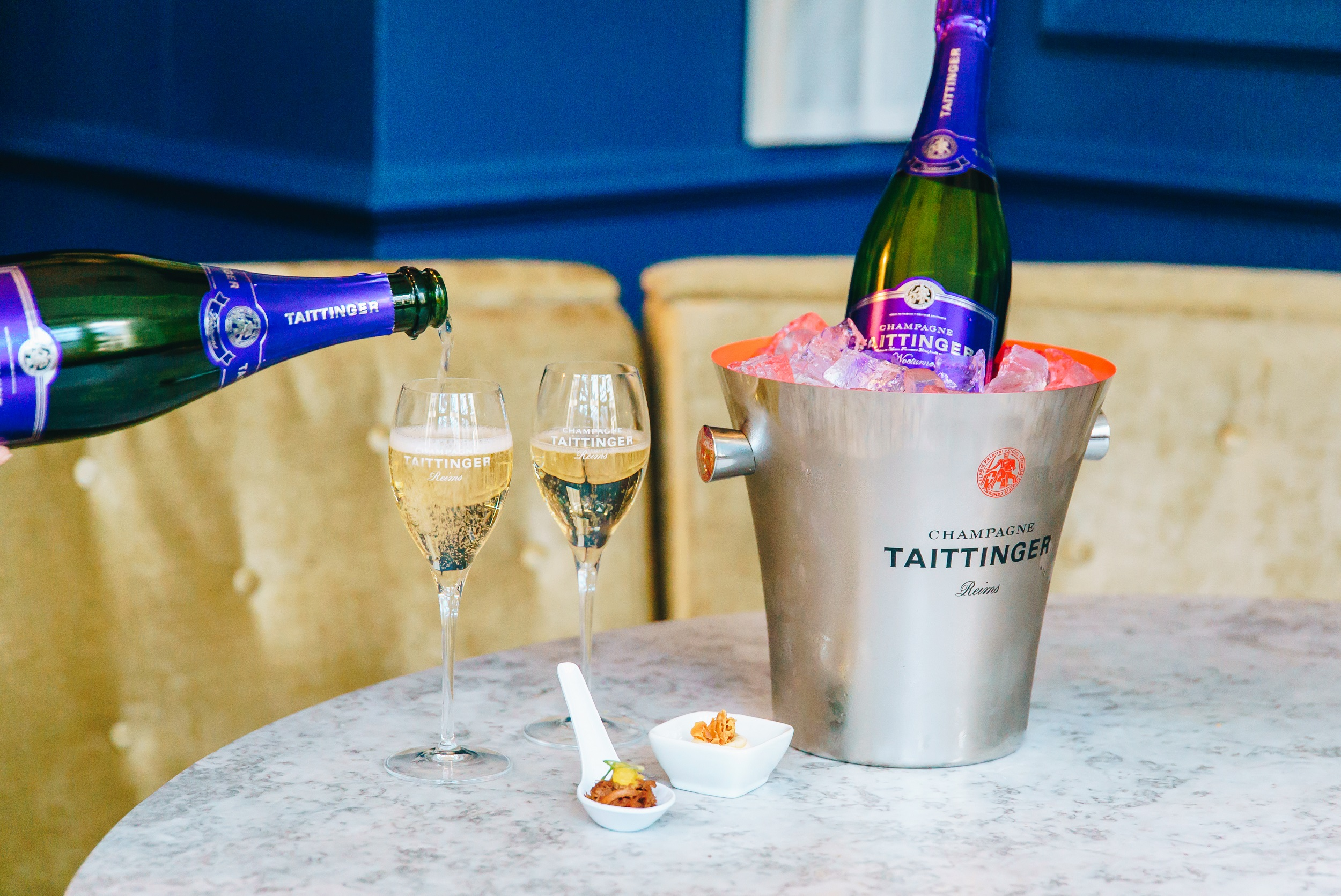 Bottle of Taittinger Brut Reserve NV in ice bucket with canapes